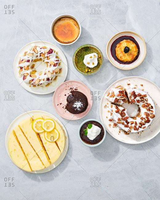 Variety of desserts served on gray background