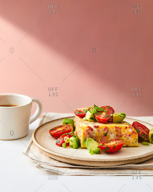 Frittata slice with meat, avocado and tomato