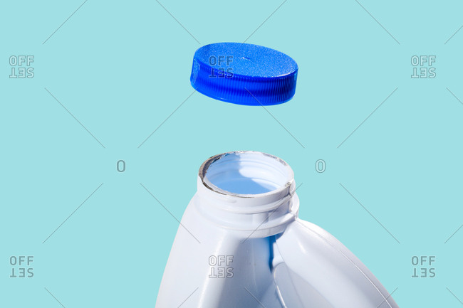 Bleach and cap on light blue background