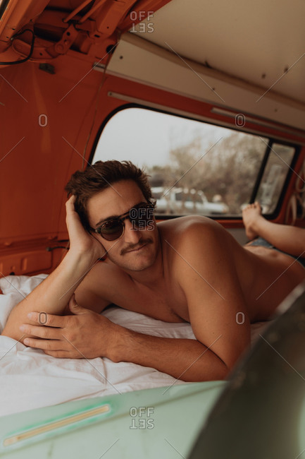 Young male surfer lying in back of recreational vehicle at beach, portrait, Jalama, California, USA