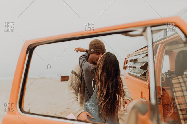 Young couple kissing by recreational vehicle at beach, Jalama, California, USA