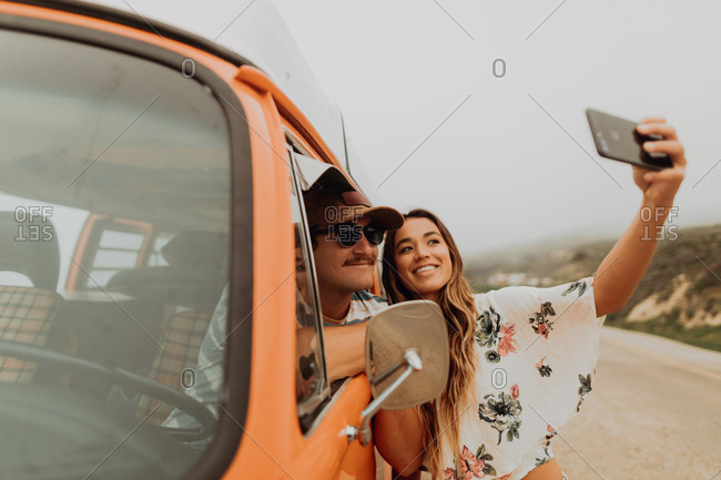 Young couple on roadside in recreational vehicle taking smartphone selfie,  portrait, Jalama, California, USA