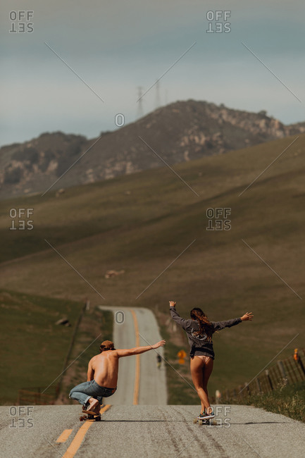 Young skateboarder couple skateboarding down rural road, rear view, Jalama, California, USA