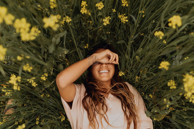Young woman lying in yellow wildflower field, overhead portrait, Jalama, California, USA