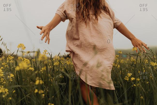 Young woman walking in yellow wildflower field, rear view, Jalama, California, USA