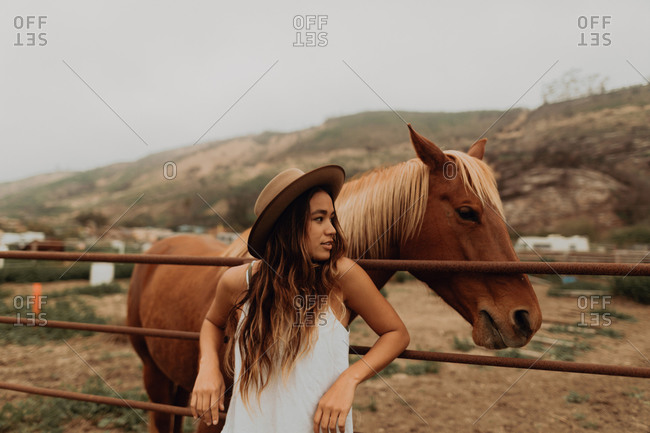 Young woman in felt hat leaning against fence next to horse, Jalama, California, USA