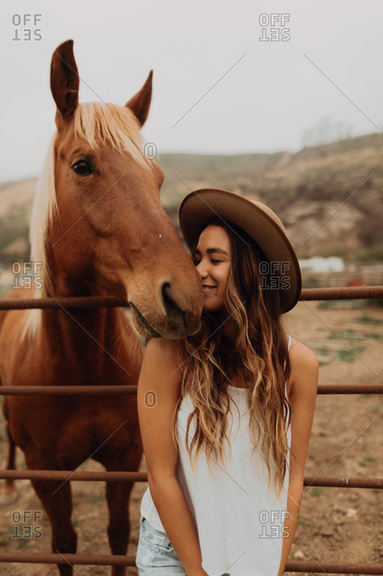 Young woman in felt hat nose to nose with horse, Jalama, California, USA