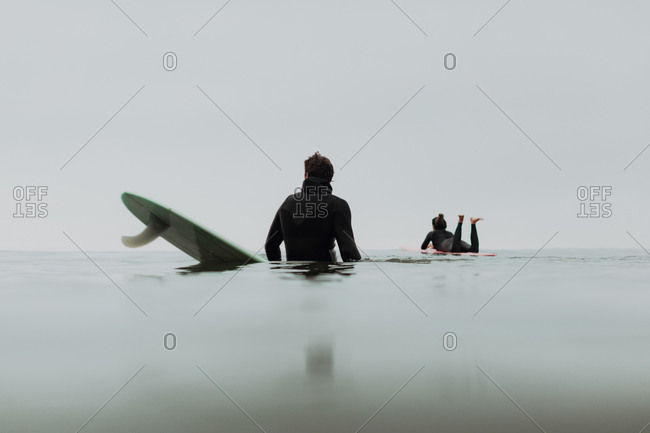 Young surfer couple on surfboards in calm misty sea, Ventura, California, USA