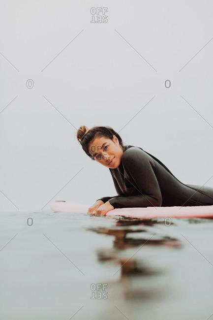 Young female surfer lying on surfboard in calm misty sea, portrait, Ventura, California, USA