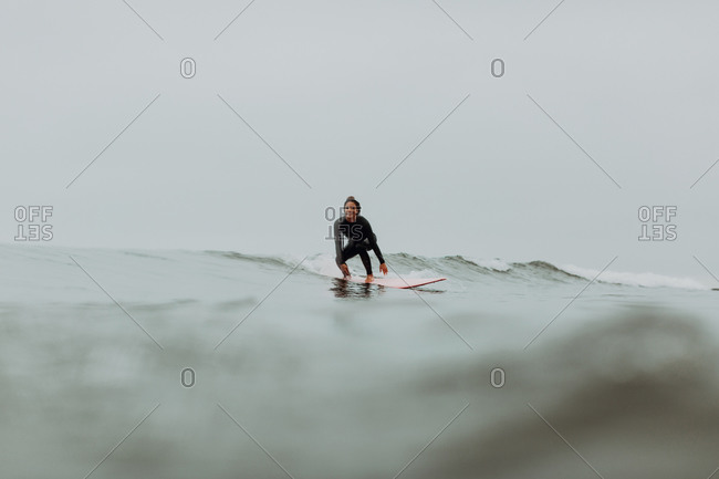 Young female surfer surfing on misty calm sea, Ventura, California, USA