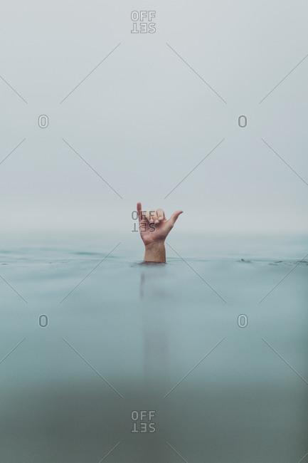 Male scuba diver's hand signaling decompression from sea, Ventura, California, USA