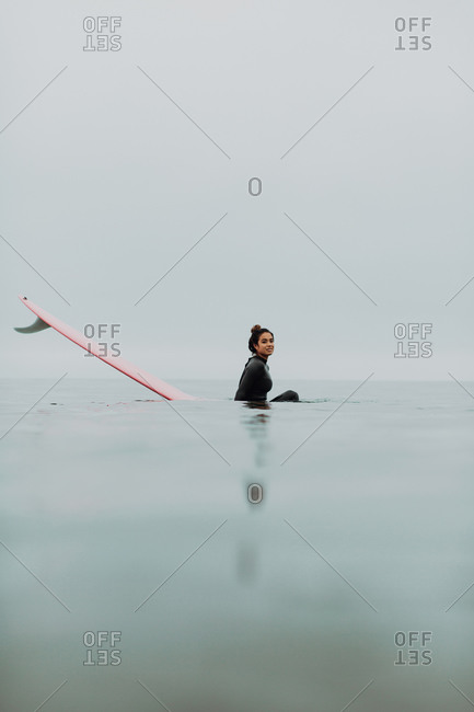 Young female surfer sitting on surfboard in calm misty sea, portrait, Ventura, California, USA