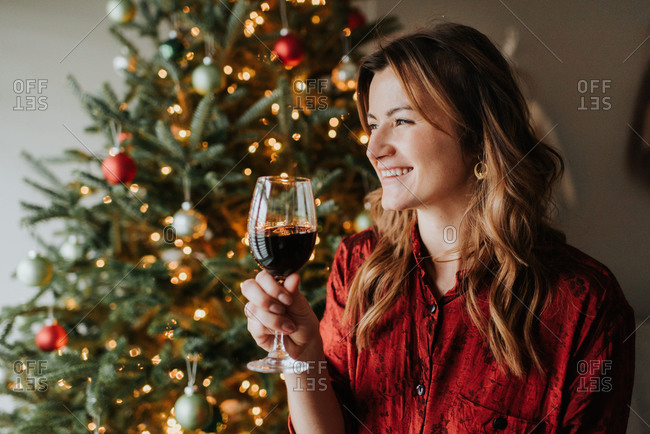 Woman drinking wine beside decorated Christmas tree