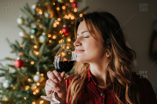 Woman smelling glass of wine beside decorated Christmas tree