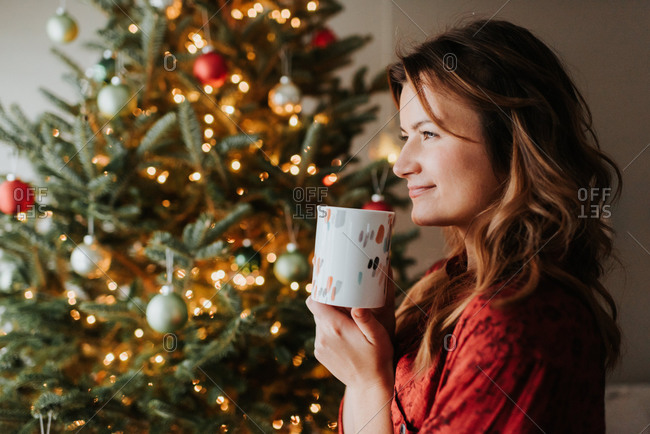 Woman drinking coffee beside decorated Christmas tree