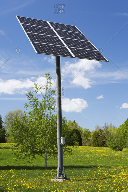 Solar energy collector panels mounted on metal post in field, Quebec, Canada