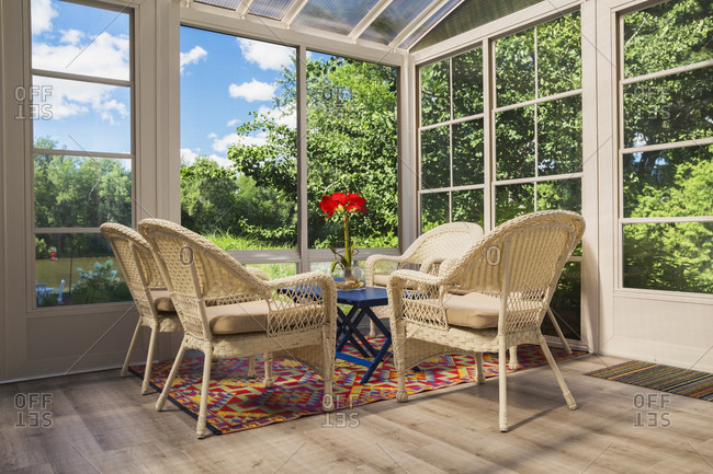 Beige wicker armchairs and blue wooden table in sunroom