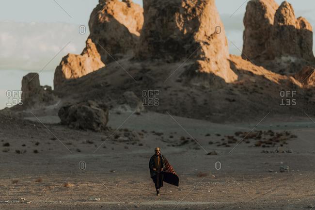 Man walking across desert, Trona Pinnacles, California, US