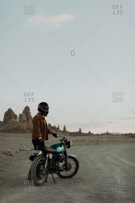 Motorcyclist beside stationary bike in desert, Trona Pinnacles, California, US
