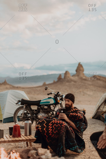 Motorcyclist road trippers around camp fire, Trona Pinnacles, California, US