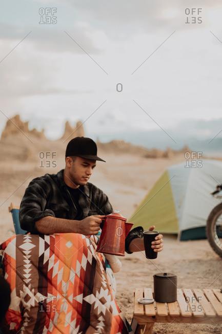 Man pouring hot water into mug, Trona Pinnacles, California, US