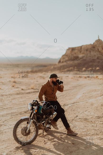 Motorcyclist enjoying drink on stationary bike, Trona Pinnacles, California, US