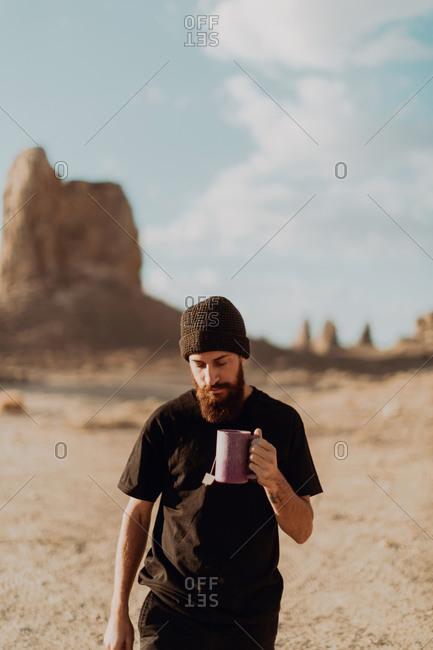 Man with mug of tea in desert, Trona Pinnacles, California, US