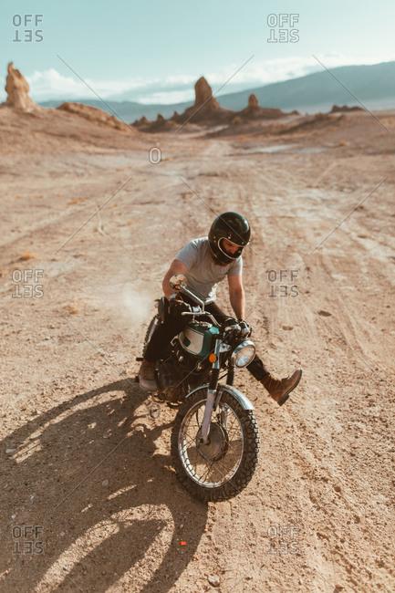 Motorcyclist enjoying stunts, Trona Pinnacles, California, US