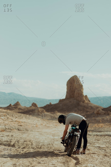 Motorcyclist bending over bike in desert, Trona Pinnacles, California, US