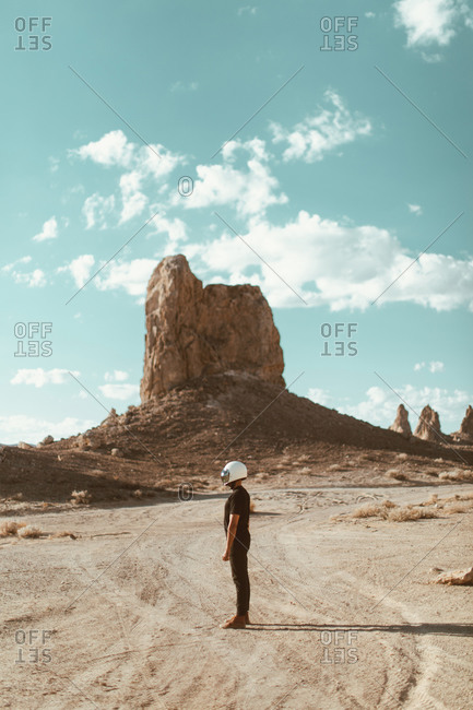 Motorcyclist standing in desert, Trona Pinnacles, California, US