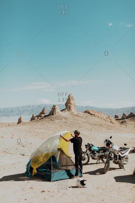 Motorcyclist setting up tent, Trona Pinnacles, California, US