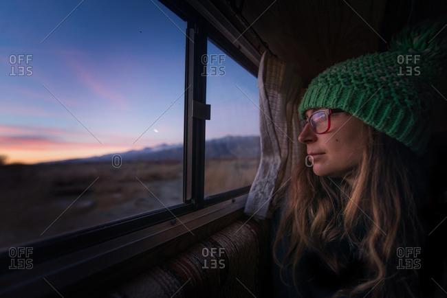Woman keeping warm inside campervan in desert, Sierra Nevada, Bishop, California, USA