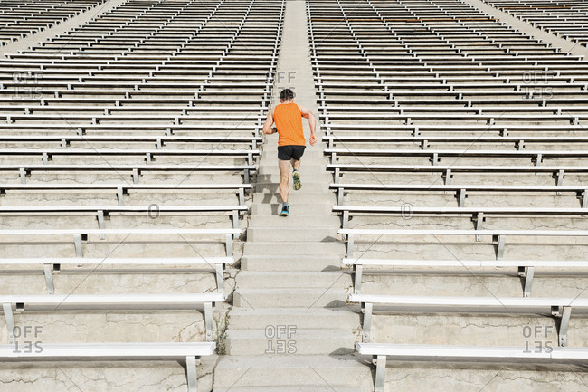 Young male runner running up stadium stairway, rear view
