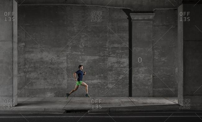 Young male runner running through underpass