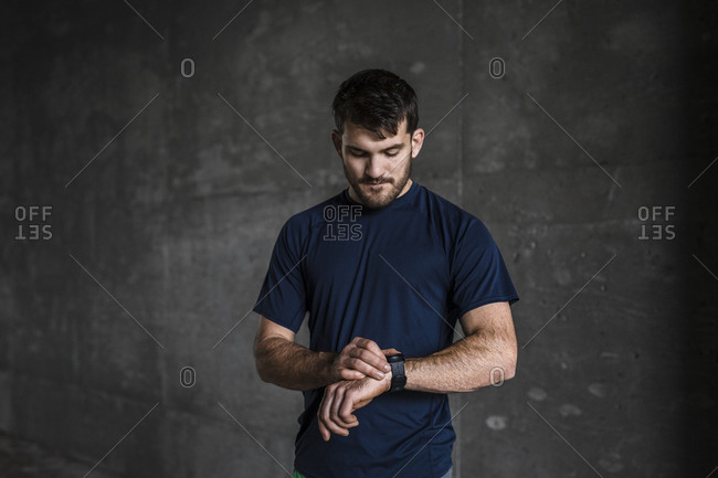 Young male runner checking smartwatch in underpass
