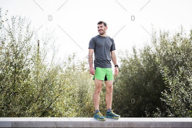 Young male runner standing on wall smiling