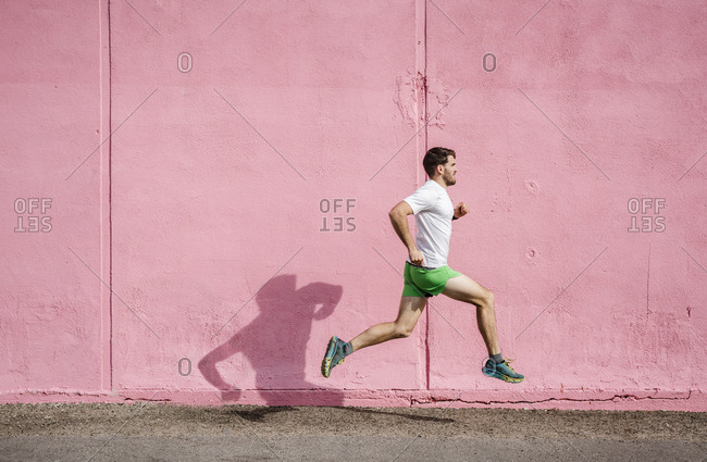 Young male runner running past pink wall
