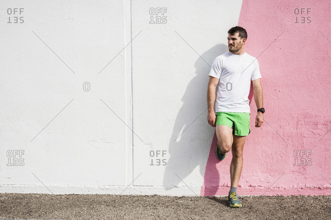 Young male runner leaning against pink and white wall