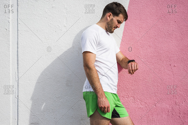 Young male runner leaning against wall checking smartwatch