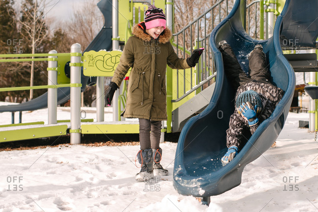 Girl watching brother headfirst on playground slide in snow