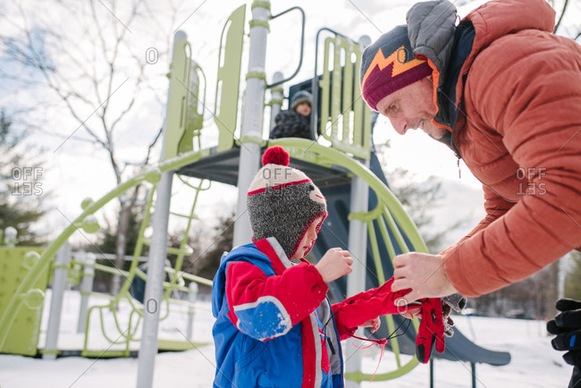 Father putting on boy's gloves by playground slide in snow