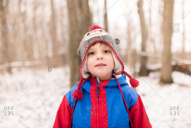 Boy in knit hat by snow covered forest, portrait