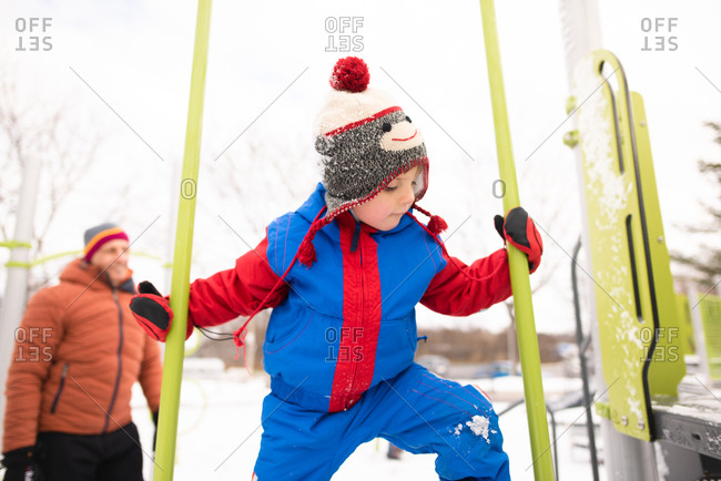 Boy with father climbing up playground slide in snow