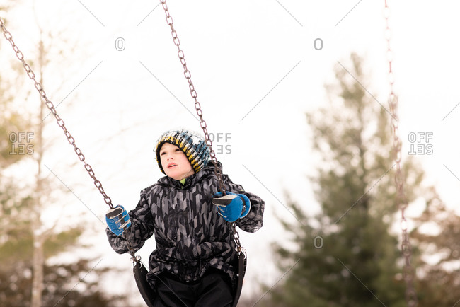 Boy in knit hat swinging on playground swing in winter