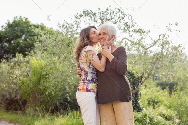 Mature woman kissing mother on cheek in garden