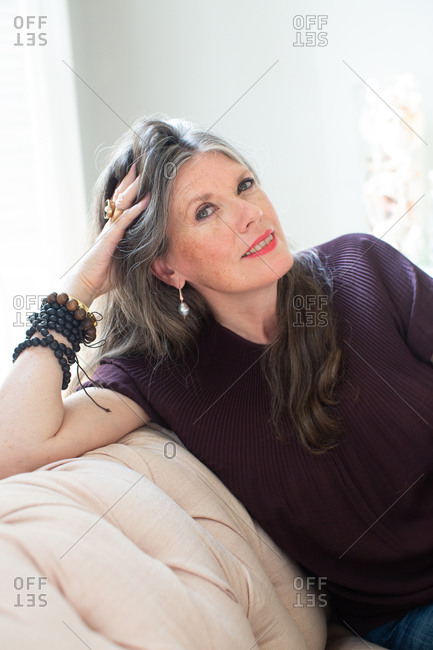 Stylish mature woman with long grey hair sitting on sofa, portrait