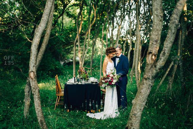 Romantic bride and groom by forest reception table