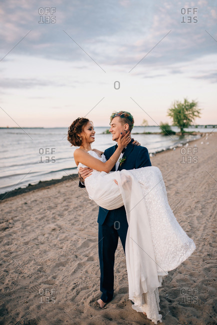 Romantic groom carrying bride on lakeside, Lake Ontario, Toronto, Canada