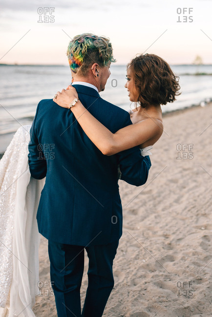 Romantic groom carrying bride on lakeside, rear view,  Lake Ontario, Toronto, Canada