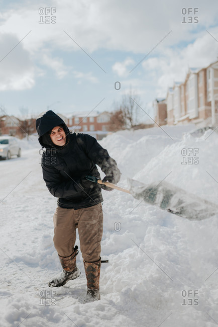 Man clearing snow-covered road with shovel, Toronto, Canada